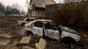 Burnt cars sit next to a house near Penacova, northern Portugal, Monday, Oct. 16 2017. Wildfires in Portugal killed at least 27 people, injured dozens more and left an unconfirmed number of missing in the country's second such tragedy in four months, officials said Monday. (AP Photo/Sergio Azenha)