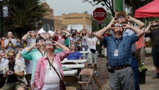 The sun peeks through the clouds as people wearing solar glasses watch the solar eclipse in Falls City, Neb., Aug. 21, 2017. (Nati Harnik/AP)