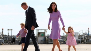 In this Friday, July 21, 2017 file photo Prince William, second left, and his wife Kate, the Duchess of Cambridge, second right, and their children, Prince George, left, and Princess Charlotte, right are on their way to board a plane in Hamburg, Germany. T( Christian Charisius/Pool Photo via AP, File)