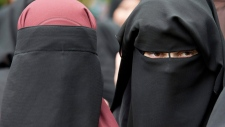 FILE - In this June 28, 2014 file photo veiled women attend a speech by preacher Pierre Vogel, in Offenbach, near Frankfurt, Germany. A law that forbids any kind of full-face covering, including Islamic veils such as the niqab or burqa, has come into force in Austria Sunday, Oct. 1, 2017. Only a small number of Muslim women in Austria wear full-face veils, but they have become a target for right-wing groups and political parties. France and Belgium have similar laws and the nationalist Alternative for Germany party is calling for a burqa ban there too. (Boris Roessler/dpa via AP,file)