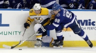 Nashville Predators center Kevin Fiala (22) and Tampa Bay Lightning defenseman Mikhail Sergachev (98) battle for the puck during the third period of an NHL preseason hockey game Friday, Sept. 22, 2017, in Tampa, Fla. (AP Photo/Chris O'Meara)