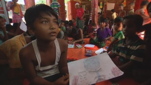 Monsur Ali, 11, shows a drawing he made recalling what happened after he and his family were forced to flee Myanmar.