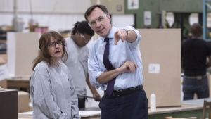 Finance Minister Bill Morneau chats with a worker at a kitchen counter factory, in Montreal on Oct. 17, 2017. (Paul Chiasson / THE CANADIAN PRESS)