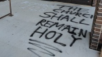A spray-painted Bible verse is seen outside Parkminster United Church in Waterloo. (Marta Czurylowicz / CTV Kitchener)