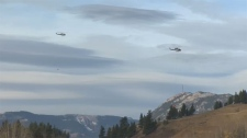 Helicopters fight a wildfire burning in Crowsnest Pass from the air and officials say it now covers over 100 hectares.