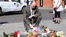 Kingston Mayor Bryan Paterson places flowers on The Tragically Hip commemorative plaque in Kingston, Ont., on Wednesday, October 18, 2017. Gord Downie, the poetic lead singer of the Tragically Hip whose determined fight with brain cancer inspired a nation, has died at the age of 53. THE CANADIAN PRESS/Lars Hagberg