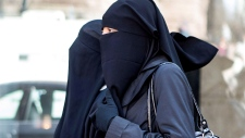 Unidentified women wear niqabs outside an Ontario court house in Toronto on Tuesday April 23, 2013. An Ontario judge has ruled that a woman must remove her face-covering veil to testify against the men she is accusing of sexual assault.THE CANADIAN PRESS/Chris Young