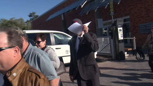 Tyson Lawlor covers his face as he leaves a courthouse in Barrie, Ont. on Wednesday, Oct. 18, 2017 after being found guilty. (Mike Walker/ CTV Barrie)