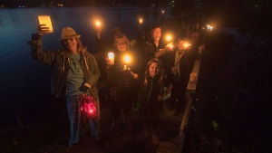 Fans of the Tragically Hip gather for a candlelight vigil by the water's edge in Bobcaygeon Ont. to pay tribute to singer Gord Downie who died on Tuesday night at the age of 53, Wednesday, October 18, 2017. THE CANADIAN PRESS/Fred Thornhill