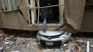 Rodrigo Diaz Mejia climbs over a crushed car into what was a second-story apartment felled by the earthquake at 517 Tokio street in the Portales Norte neighbourhood of Mexico City on Wednesday, Oct. 18, 2017. (AP / Rebecca Blackwell)