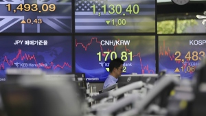 A currency trader walks by the screens showing the Korea Composite Stock Price Index (KOSPI), right, and the foreign exchange rates at the foreign exchange dealing room in Seoul, South Korea, Thursday, Oct. 19, 2017. (AP / Lee Jin-man)