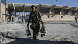 A member of U.S.-backed Syrian Democratic Forces (SDF) carries explosives at a stadium that that was the site of Islamic State fighters' last stand in the city of Raqqa, Syria on Wednesday, Oct. 18, 2017. (AP / Asmaa Waguih)