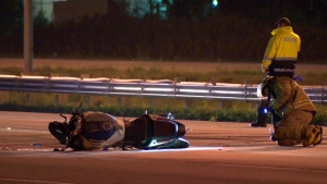 A firefighter inspects a motorcycle following a deadly crash on Highway 15 in Mirabel on Oct. 19, 2017 (CTV Montreal/Cosmo Santamaria)