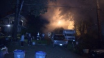 Firefighters battle a blaze that engulfed a home in Surrey late Wednesday night.