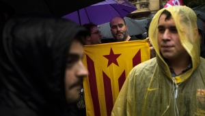 Protesters, one of them holding a pro-independence flag, gather at the gates of the Spanish central government offices in Barcelona as they protest against the National Court's decision to imprison civil society leaders, Spain, Thursday, Oct. 19, 2017. (AP / Emilio Morenatti)