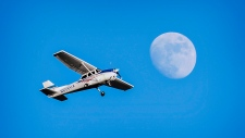 A Cessna 172 airplane flies Sunday, Jan. 12, 2014 over a nearly full moon as it leaves the Bowling Green/Warren County Regional Airport in Bowling Green, Ky. (AP Photo/Daily News, Joshua Lindsey)