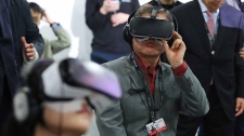 South Korean President Moon Jae-In (C) wears a virtual reality (VR) headset during a VR event at the Busan International Film Festival. (STR/YONHAP/AFP)