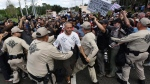 Randy Furniss, of Idaho, wearing a shirt with swastikas, is pulled through the line of Florida Highway Patrol officers for his safety after an angry mob followed him off the University of Florida campus in Gainesville, Fla., where white nationalist Richard Spencer spoke on Thursday, Oct. 19, 2017. (Bob Self/The Florida Times-Union via AP)
