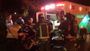 Emergency crews are seen transporting a Toronto firefighter to hospital.