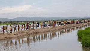 Rohingya Muslims, who spent four days in the open after crossing over from Myanmar into Bangladesh, carry their children and belongings after they were allowed to proceed towards a refugee camp, at Palong Khali, Bangladesh, Thursday, Oct. 19, 2017. More than 580,000 refugees have arrived in Bangladesh since Aug. 25, when Myanmar security forces began a scorched-earth campaign against Rohingyavillages. Myanmar's government has said it was responding to attacks by Muslim insurgents, but the United Nations and others have said the response was disproportionate. (AP Photo/Dar Yasin)