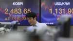 A currency trader walks by the screens showing the Korea Composite Stock Price Index (KOSPI), left, and the foreign exchange rate between U.S. dollar and South Korean won at the foreign exchange dealing room in Seoul, South Korea on Thursday, Oct. 19, 2017. (AP / Lee Jin-man)