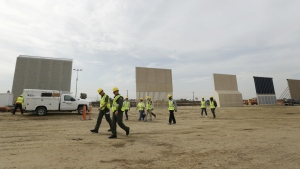 People pass border wall prototypes as they stand near the border with Tijuana, Mexico on Thursday, Oct. 19, 2017. (AP / Gregory Bull)