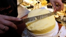 A woman cuts a slice of butter on a market in Bayonne, southwestern France, Friday, 20 Oct., 2017. French pastries and butter have become so popular abroad that the increased demand led to a mini shortage of the dairy product in French supermarkets. (AP Photo/Bob Edme)