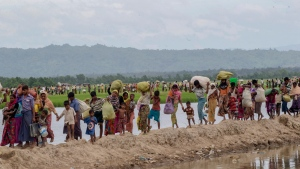 Rohingya Muslims, who spent four days in the open after crossing over from Myanmar into Bangladesh, carry their belongings after they were allowed to proceed towards a refugee camp, at Palong Khali, Bangladesh, Oct. 19, 2017. (Dar Yasin/AP)