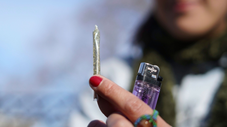 Luisina Mezquita shows a joint made of legal marijuana she just bought at a pharmacy in Montevideo, Uruguay, Wednesday, July 19, 2017. (AP Photo/Matilde Campodonico)