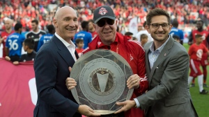 Toronto FC President Bill Manning (left), Maple Leafs Sports and Entertainment chairman Larry Tanenbaum (centre) and Toronto FC general manager Tim Bezbatchenko pose with the Supporters' Shield, awarded to the MLS team with the most points over the regular season, on Oct.15, 2017. (THE CANADIAN PRESS / Frank Gunn)