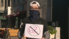 A protester wearing a neck warmer demonstrates against Bill 62 in Montreal on Oct. 20, 2017.
