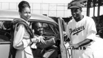 In this Sept. 23, 1947, file photo, Brooklyn Dodgers baseball player Jackie Robinson, right, receives the keys to a car from tap dancer Bill Bojangles Robinson as Jackie Robinson's wife, Rachel, looks on at Ebbets Field in New York.  (AP Photo/Harry Harris, File)