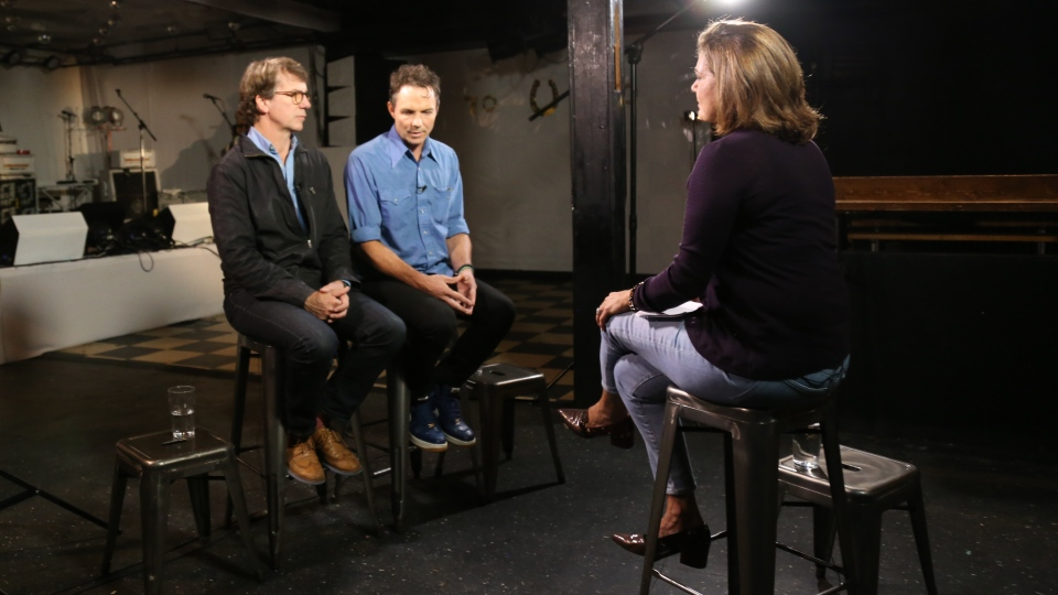 Mike Downie (left) and Patrick Downie speak to Lisa LaFlamme in Toronto's Horseshoe Tavern in Toronto, on Friday, Oct. 20, 2017. (Rosa Hwang / CTV)