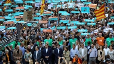 Catalan President Carles Puigdemont, front row, center, takes part at a march to protest against the National Court's decision to imprison civil society leaders, in Barcelona, Spain, Saturday, Oct. 21, 2017. The Spanish government moved decisively Saturday to use a previously untapped constitutional power so it can take control of Catalonia and derail the independence movement led by separatist politicians in the prosperous industrial region.(AP Photo/Emilio Morenatti)