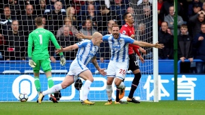 Huddersfield Town's Aaron Mooy, center, celebrates scoring his side's first goal of the game during the English Premier League soccer match between Huddersfield Town and Manchester United at the John Smith's stadium in Huddersfield, England, Oct. 21, 2017. (Nigel French / PA via AP)