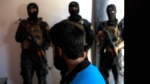 In this file picture taken on Friday, July 21, 2017, Kurdish soldiers from the Anti-Terrorism Units, background, stand in front a blindfolded Turkish suspected Islamic State member, Onur, at a security center, in Kobani, Syria. (Hussein Malla/AP Photo)