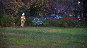 A firefighter looks at a Cessna that crashed in Saint-Lazare Saturday afternoon.