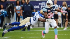 Toronto Argonauts running back Martese Jackson (30) runs past Winnipeg Blue Bombers linebacker Kyle Knox (50) during first half CFL football action in Toronto on Saturday, October 21, 2017. THE CANADIAN PRESS/Nathan Denette