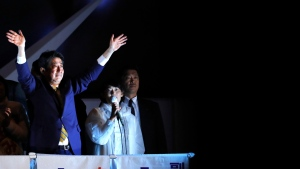 Japan's Prime Minister and President of the ruling Liberal Democratic Party Shinzo Abe waves to the crowd in support for his party's candidate during an election campaign for the upcoming lower house election in Tokyo. (AP Photo / Eugene Hoshiko)