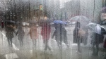 Pedestrians carrying umbrellas to shield themselves from the rain are seen through a cafe window covered with rain and steam in Vancouver, B.C. (THE CANADIAN PRESS / Darryl Dyck)