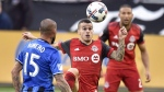 Toronto FC's Sebastian Giovinco (centre) plays the ball as Montreal Impact midfielder Andres Romero (15) looks on during MLS soccer action in Toronto on October 15, 2017. (Frank Gunn/The Canadian Press)