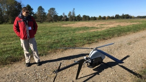 Nick Brown, a drone pilot for Pulse Aerospace of Lawrence, Kan., stands beside a Pulse Vapor unmanned aircraft at Griffiss International Airport in Rome, N.Y. on Oct. 17, 2017. (AP / Mary Esch)