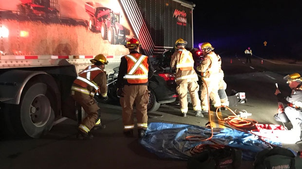 1 person trapped after car drives under transport truck