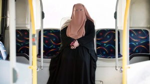 Warda Naili poses for a photograph on a city bus in Montreal, Saturday, October 21, 2017. Warda Naili says the first time she donned a niqab six years ago, it became a part of her. The Quebec woman, a convert to Islam, said she decided to cover her face out of a desire to practice her faith more authentically and to protect her modesty. (Graham Hughes / THE CANADIAN PRESS)