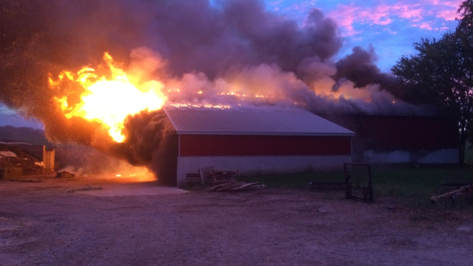 Firefighters battle a barn fire north of Woodstock, Ont., on Monday, Oct. 23, 2017. (Simon Visser)
