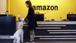 Amazon employee gives her dog a biscuit at a company building in Seattle, on Oct. 11, 2017. (Elaine Thompson / AP)