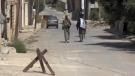 Two Syrian soldiers walking in the street of Qaryatayn, Syria, on Oct 21, 2017. (AP)