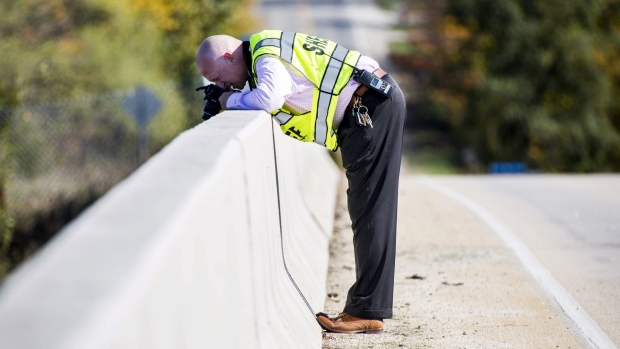 Genesee County Sheriff's Office investigator takes photos from an overpass where Dodge Road crosses Interstate 75 near the scene of a traffic fatality, in in Vienna Township, Mich., on Friday, Oct. 20, 2017. (Terray Sylvester/The Flint Journal-MLive.com via AP)