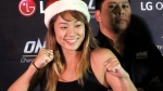 FILE - In this Dec. 10, 2015, file photo, mixed martial arts fighter Angela Lee poses wearing a Santa hat, following a weigh-in ceremony for her One Championship bout, at the Mall of Asia Arena at suburban Pasay city south of Manila, Philippines. (AP Photo/Bullit Marquez, File)