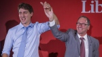 Richard Hebert, Liberal candidate for the byelection in the Lac-Saint-Jean riding, right, cheers with Prime Minister Justin Trudeau during a Liberal party rally in Dolbeau-Mistassini, Que, on Thursday, October 19, 2017. (Francis Vachon/The Canadian Press)